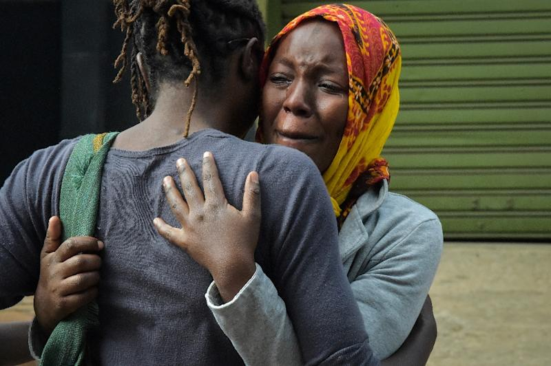 Relatives sob as they identify the bodies of the victims of the bomb and gun attack on a hotel complex in Kenya (AFP Photo/SIMON MAINA                         )