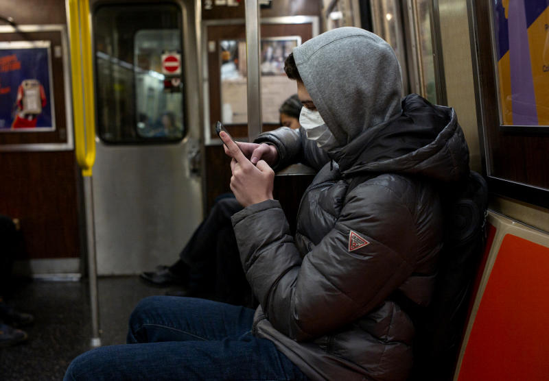 Image: A man wearing a face mask reads his phone on the subway in New York on Feb. 2, 2020. (Robert Nickelsberg / Getty Images file)