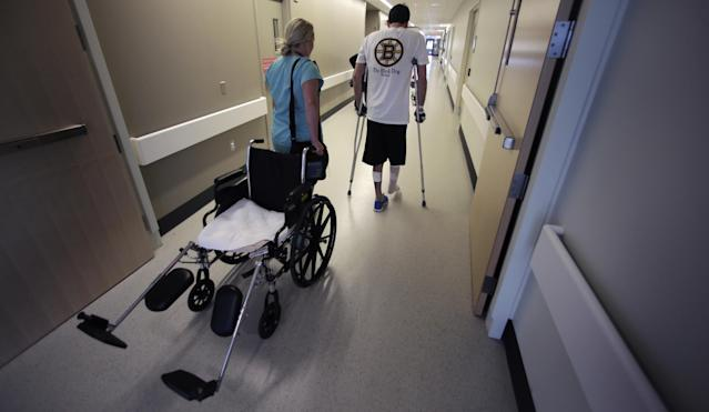 "In this Wednesday, May 22, 2013 photo, Boston Marathon bombing survivor Pete DiMartino, of Rochester, N.Y., is followed by his physical therapist Julia Broyer as he finishes a physical therapy session at the Spaulding Rehabilitation Hospital in Boston. DiMartino was injured in an explosion near the finish line, which blew away much of one leg and burned the other. ""I don't want anybody feeling sorry for me,"" he said. ""... I want people to see that this has made me a better person and I want people to become better people through what they see through me."" (AP Photo/Charles Krupa)"