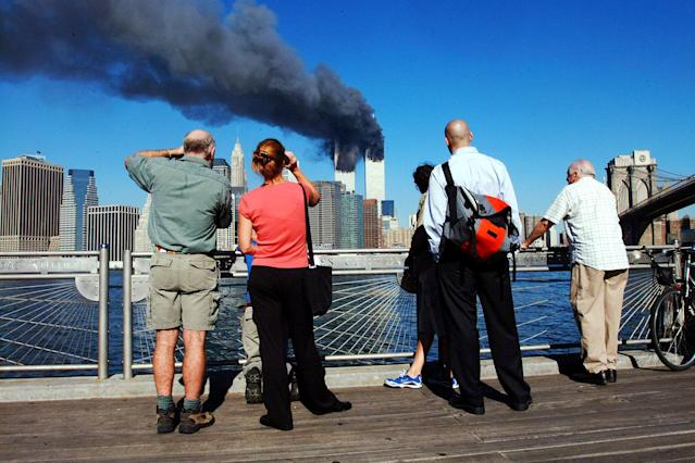 <p>Pedestrians on the waterfront in Brooklyn, New York, look across the East River to the burning World Trade Center towers Sept. 11, 2001 after a terrorist attack. (Photo: Henny Ray Abrams/AFP/Getty Images) </p>