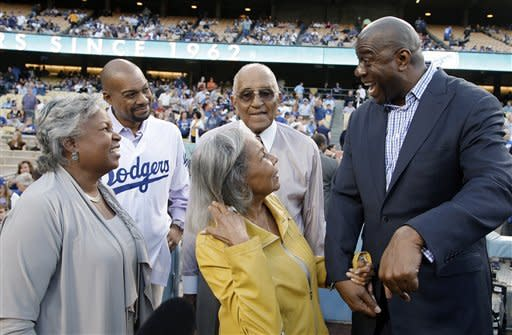 "Los Angeles Dodgers new co-owner Earvin ""Magic"" Johnson, right, talks with, from left, Jackie Robinson's daughter Sharon Robinson; grandson Jesse Sims; widow, Rachel Robinson; and Dodgers great Don Newcombe at Dodger Stadium, before the Dodgers' baseball game against the San Francisco Giants in Los Angeles on Monday, May 7, 2012. (AP Photo/Reed Saxon)"