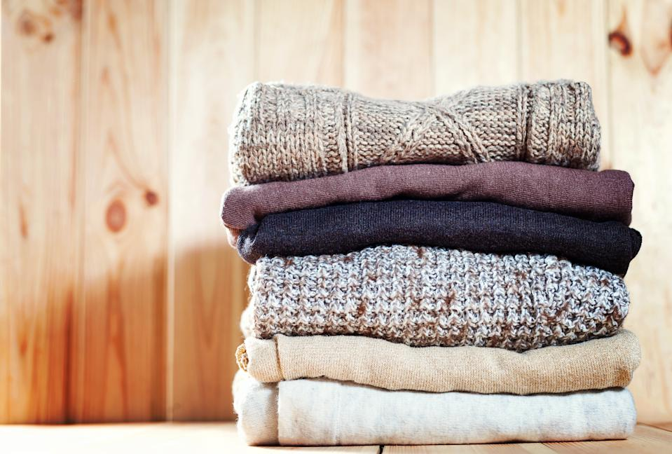 Knit cozy sweater folded in a pile on wooden background .Warm the concept. Copyspace.