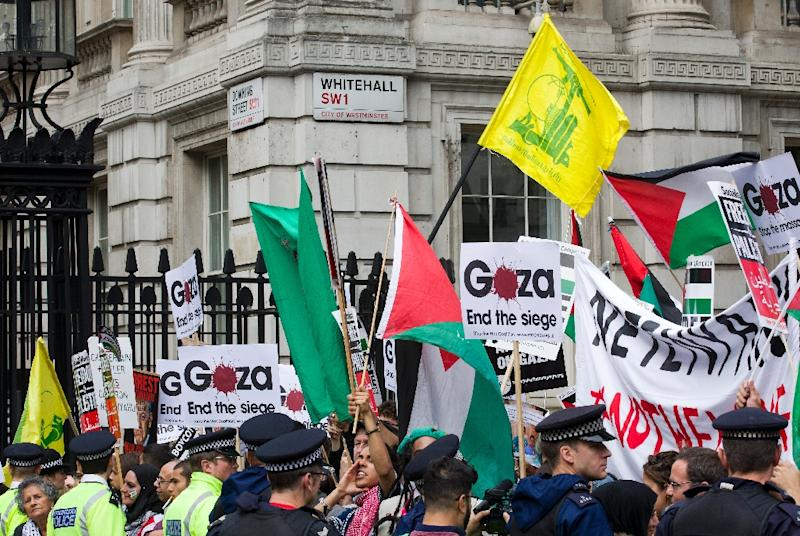 Pro-Palestinian demonstrators carry Palestinian flags and the yellow flag of Lebanese Shiite militant group Hezbollah as they rally outside the gates of Downing Street in London on September 9, 2015