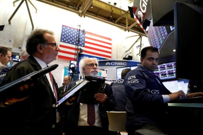 FILE PHOTO: Traders work on the floor of the New York Stock Exchange, (NYSE) in New York