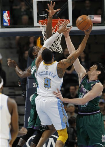 Denver Nuggets guard Andre Iguodala, center, tries to drive for a shot as Milwaukee Bucks center Larry Sanders, left, and forward Ersan Ilyasova, right, of Turkey, defend during the first quarter of an NBA basketball game in Denver on Tuesday, Feb. 5, 2013. (AP Photo/David Zalubowski)