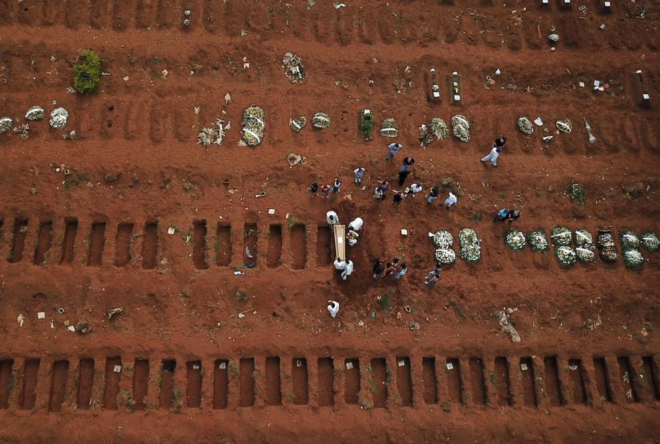 An aerial view shows gravediggers wearing protective suits carrying a coffin during burial of a person who died from the coronavirus disease (COVID-19) at Vila Formosa cemetery, in Sao Paulo, Brazil, March 23, 2021. Picture taken March 23, 2021. Picture taken with a drone. REUTERS/Amanda Perobelli