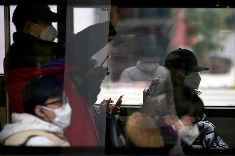 People wear protective masks while they travel on a bus in Shanghai