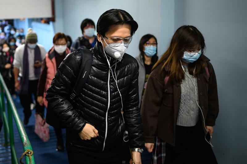 Passengers wearing face masks alight from a ferry in Hong Kong on February 5, 2020, as a preventative measure following a virus outbreak which began in the Chinese city of Wuhan. - More Chinese cities hunkered down by fencing off streets and telling millions of people to stay home as the death toll from the new coronavirus soared to nearly 500 on February 5. Hong Kong now has 18 confirmed infections, the majority people who were infected in mainland China. (Photo by Philip FONG / AFP) (Photo by PHILIP FONG/AFP via Getty Images)
