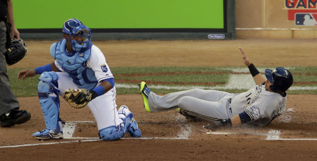National League's Aramis Ramirez, of the Milwaukee Brewers, scores in front of American League catcher Salvador Perez, left, during the second inning of the MLB All-Star baseball game, Tuesday, July 15, 2014, in Minneapolis. (AP Photo/Paul Sancya)