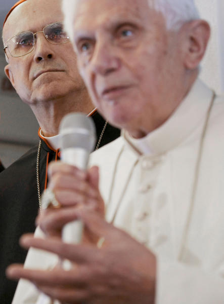 """FILE - In this March 23, 2012 file photo, Vatican Secretary of State Tarcisio Bertone, left, looks on as Pope Benedict XVI talks to journalists during a press conference aboard the flight to Silao, Mexico. An already sordid scandal over leaked Vatican documents took a Hollywood-like turn Saturday, May 26, 2012 with confirmation that the pope's own butler had been arrested after documents he had no business having were found in his Vatican City apartment. The """"Vatileaks"""" scandal has seriously embarrassed the Vatican at a time when it is trying to show the world financial community that it has turned a page and shed its reputation as a scandal plagued tax haven. Bertone, 77, has been blamed for a series of gaffes and management problems that have plagued Benedict's papacy and, according to the leaked documents, generated a not inconsiderable amount of ill will directed at him from other Vatican officials. (AP Photo/Gregorio Borgia, File)"""