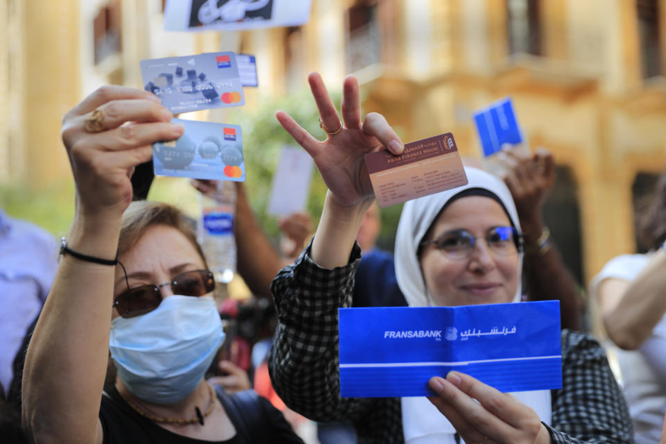 Lebanese depositors show their ATM and Visa cards as they protest outside a bank, in Beirut, Lebanon, Friday, Sept. 24, 2021. Dozens of Lebanese depositors protested throwing eggs and tomatoes on a number of private banks in central Beirut, demanding to have access to their deposits which have been blocked under informal capital controls since the country's financial and economic crisis began in late 2019. (AP Photo/Hussein Malla)