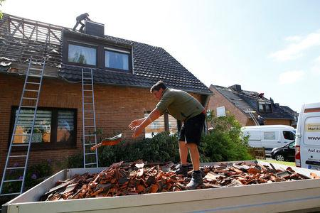 Workers remove roof tiles after a tornado last night hit the area of Boisheim, west of Duesseldorf, Germany, May 17, 2018.    REUTERS/Thilo Schmuelgen