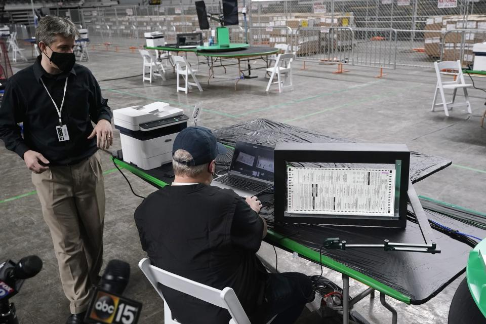 Cyber Ninjas owner Doug Logan, left, a Florida-based consultancy, talks about overseeing a 2020 election ballot audit ordered by the Republican lead Arizona Senate at the Arizona Veterans Memorial Coliseum, as a Cyber Ninjas IT technician demonstrates a ballot scan during a news conference Thursday, April 22, 2021, in Phoenix. The equipment used in the November election won by President Joe Biden and the 2.1 million ballots were moved to the site Thursday so Republicans in the state Senate who have expressed uncertainty that Biden's victory was legitimate can recount them and audit the results. (AP Photo/Ross D. Franklin)