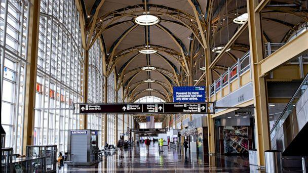 PHOTO: A handful of travelers are seen at the largely-empty Ronald Reagan Washington National Airport in Arlington, Va., due to the coronavirus pandemic, March 25, 2020. (Michael Reynolds/EPA via Shutterstock)