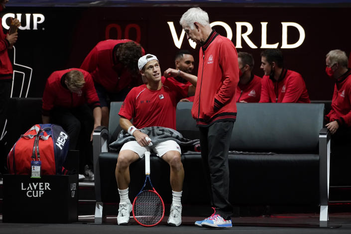 Team World's captain John McEnroe, standing, speaks to Team World's Diego Schwartzman, of Argentina, during a break in his match against Team Europe's Andrey Rublev, of Russia, at Laver Cup tennis, Friday, Sept. 24, 2021, in Boston. (AP Photo/Elise Amendola)
