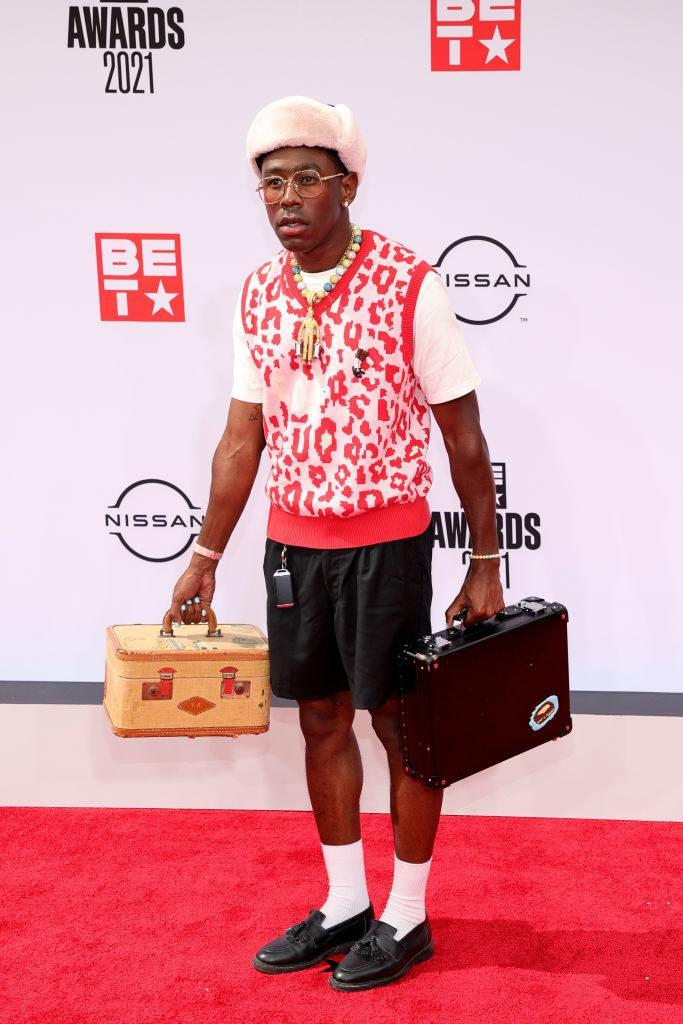 Tyler, the Creator attends the BET Awards 2021 carrying a suitcase and wearing a sweater vest and shorts