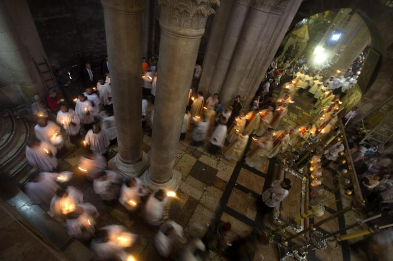 Christian clergymen hold candles during the Easter Sunday procession at the Church of the Holy Sepulchre, traditionally believed by many to be the site of the crucifixion and burial of Jesus Christ, in Jerusalem's Old City, Sunday, April 20, 2014. Millions of Christians around the world celebrated Easter commemorating the day when according to Christian tradition Jesus was resurrected in Jerusalem two millennia ago. (AP Photo/Sebastian Scheiner)