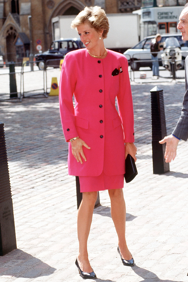 <p>First up is this stellar hot pink skirt suit with contrasting black buttons and a pocket square that Diana paired with matching pumps for a visit to Westminster in June 1990.</p>