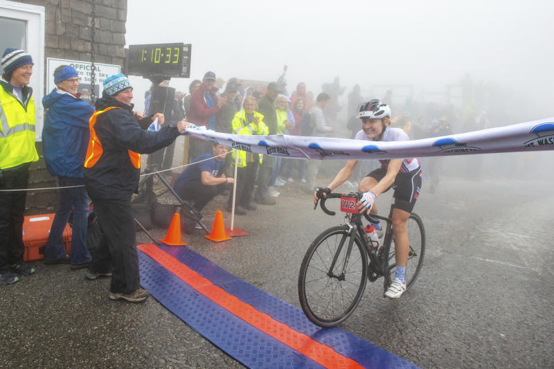 This photo provided by Joe Viger Photography, Stephanie Sydlik crosses the finish line at the Mt. Washington Bicycle Hillclimb on Saturday, Aug. 17, 2019.  Sydlik, 34, of Pittsburgh, beat the competition in the women's division of the 7.6-mile (12-kilometer) Mount Washington Auto Road Bicycle Hillclimb to the summit at 6,288 feet (1,915 meters).  (Joe Viger Photography via AP)