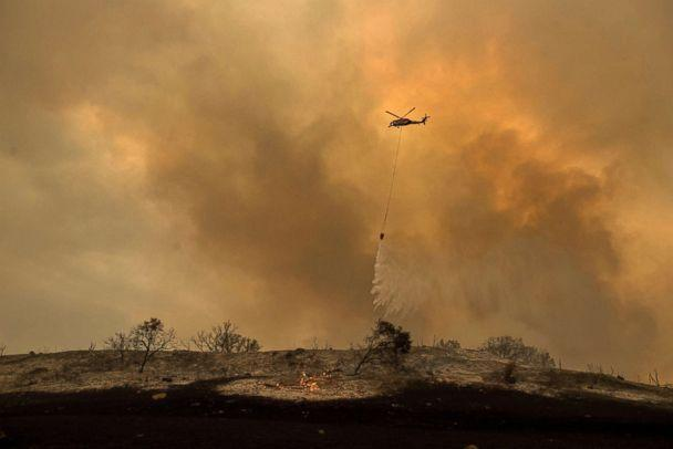 PHOTO: A helicopter drops water while trying to keep a wildfire from jumping Santa Ana Road near Ventura, Calif., Dec. 9, 2017. (Noah Berger/AP)