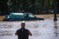 A man looks at a vehicle flooded as a result of the remnants of Hurricane Ida in a parking lot in Somerville, N.J., Thursday, Sept. 2, 2021. (AP Photo/Eduardo Munoz Alvarez)