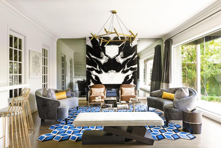 """Curved sofas by Mitchell Gold + Bob Williams provide ample space for family gatherings. The irregular edges of the rug by Carol Piper play off the coffee tables by Tom Dixon and the brass chandelier by Jonathan Browning. The showstopper is undoubtedly the book-matched marble slabs that surround the fireplace. A closer look reveals that the black-and-white stone doesn't quite reach the ceiling. """"The marble slabs were eight inches too short, so I had the contractor fill the space with wood and I hired an artist to paint the space,"""" Loya explains of the faux design moment. """"I had to improvise!"""""""