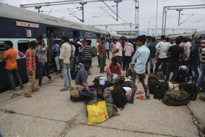 Indian migrant laborers wait at a railway station to leave the region in Jammu, India, Wednesday, Aug. 7, 2019. Indian lawmakers passed a bill Tuesday that strips statehood from the Indian-administered portion of Muslim-majority Kashmir, which remains under an indefinite security lockdown, actions that archrival Pakistan warned could lead to war. (AP Photo/Channi Anand)