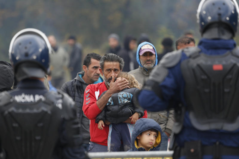 Migrant man holds a child standing in front Bosnian police cordon at the border crossing in Maljevac, Bosnia, Friday, Oct. 26, 2018. About 150 people have gathered at the Bosnian border with Croatia, hoping for the European border to open for people fleeing war and poverty.(AP Photo/Amel Emric)
