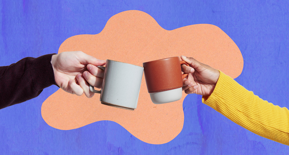 two people wearing sweaters holding coffee cups cheering each other