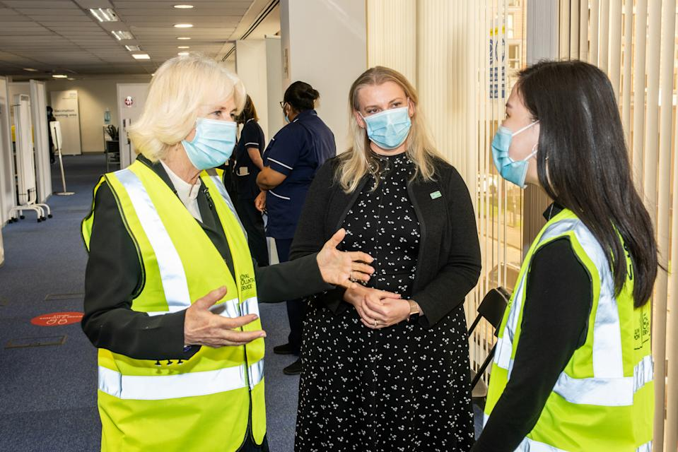 LONDON, ENGLAND - FEBRUARY 23: Camilla, Duchess of Cornwall, Royal Voluntary Service President, speaks to Liyann Ooi, a NHS Volunteer Responder Steward at Wembley Vaccination Centre on February 23, 2021 in London, England. (Photo by Philip Hartley-WPA Pool/Getty Images)