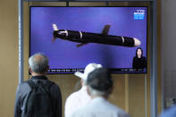 """People watch a TV screen showing a news program showing a North Korean handout photo that says, """"North Korea's long-range cruise missiles tests,"""" in Seoul, South Korea, Monday, Sept. 13, 2021. North Korea says it successfully test-fired newly developed long-range cruise missiles over the weekend, its first known testing activity in months, underscoring how it continues to expand its military capabilities amid a stalemate in nuclear negotiations with the United States. (AP Photo/Lee Jin-man)"""