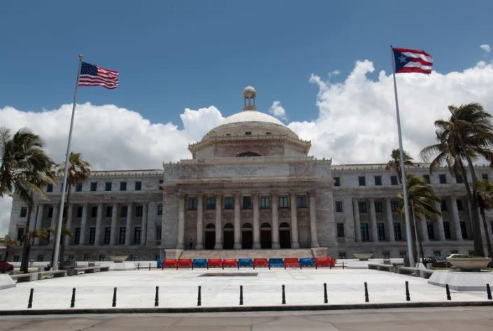 FILE PHOTO: The flags of the U.S. and Puerto Rico fly outside the Capitol building in San Juan
