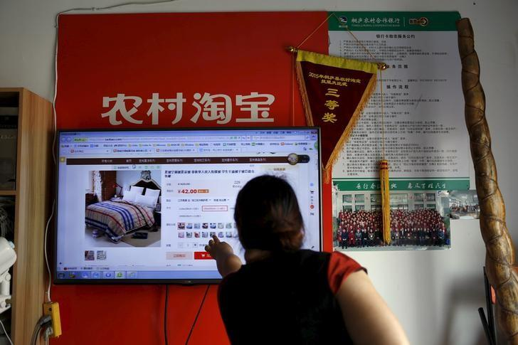 Customer points at a screen displaying a website of Alibaba's Taobao at a rural service centre in Yuzhao Village, Tonglu, Zhejiang province, China