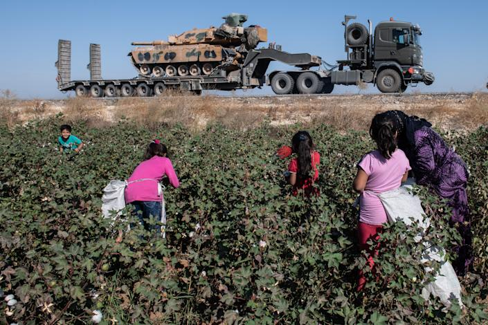 Turkish military vehicles carrying tanks head to the Syrian border as farmers work in a cotton field on Oct. 12, 2019 in Akcakale, Turkey. The military action is part of a campaign to extend Turkish control of more of northern Syria, a large swath of which is currently held by Syrian Kurds, whom Turkey regards as a threat. U.S. President Donald Trump granted tacit American approval to this campaign, withdrawing his country's troops from several Syrian outposts near the Turkish border.