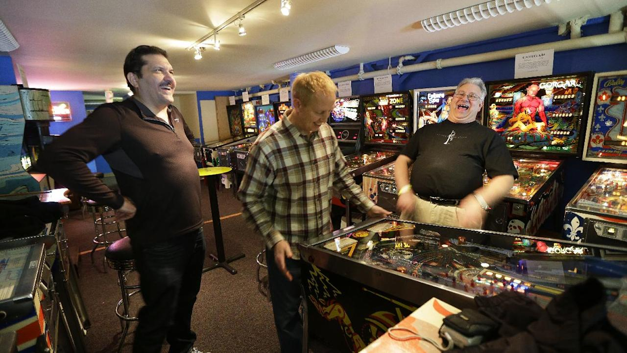 In this Dec. 16, 2013 photo, out-of-state visitors Jeff Goldsmith, left, Jim Lindquist, center, and Dave Socha, right, play the PIN BOT pinball machine, which was released in 1986, as they visit the Seattle Pinball Museum in Seattle. The museum allows visitors who pay the admission fee to play unlimited rounds on the machines, which range from the 1960s to modern-day games. (AP Photo/Ted S. Warren)