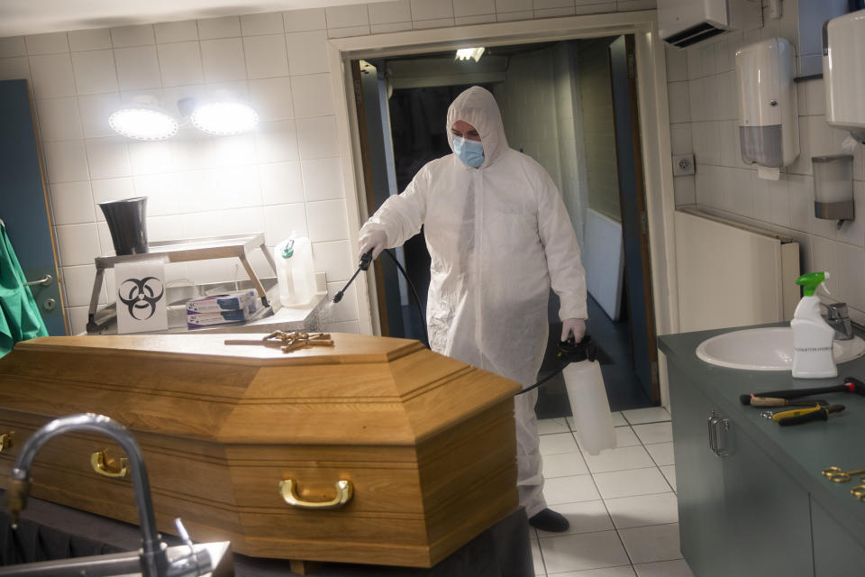 A worker, wearing a full protective equipment, disinfects the casket of someone who died of coronavirus COVID-19 at the Fontaine funeral home in Charleroi, Belgium, Tuesday, Nov. 17, 2020. One of the hardest-hit countries in Europe, Belgium has reported more than 535,000 confirmed virus cases and more than 14,400 deaths linked to the coronavirus. (AP Photo/Francisco Seco)