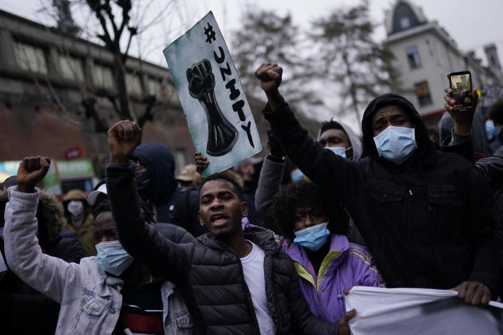 People shout slogans in the Belgium capital, Brussels, Wednesday, Jan. 13, 2021, during a protest asking for authorities to shed light on the circumstances surrounding the death of a 23-year-old Black man who was detained by police last week in Brussels. The demonstration in downtown Brussels was largely peaceful but was marred by incidents sparked by rioters who threw projectiles at police forces and set fires before it was dispersed. (AP Photo/Francisco Seco)
