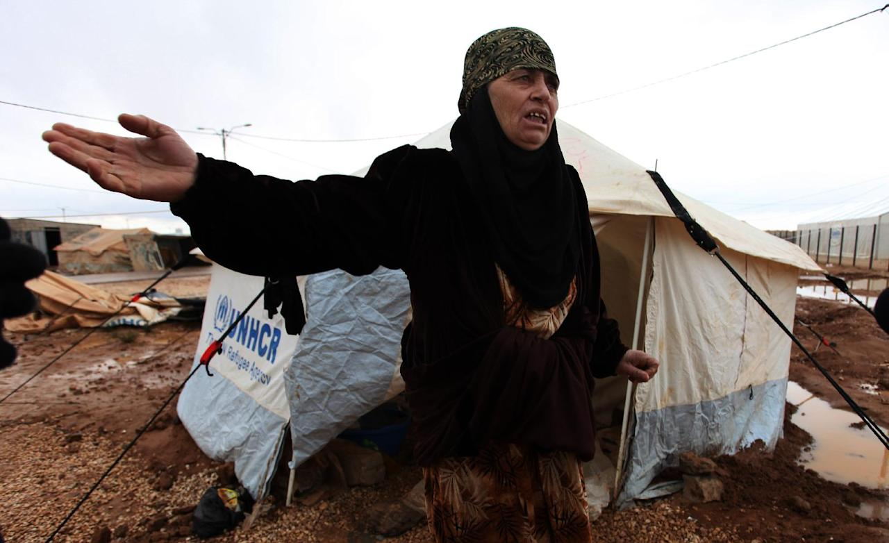 A Syrian refugee woman complains about limited winter resources, at Zaatari Syrian refugee camp, near the Syrian border in Mafraq, Jordan, Tuesday, Jan. 8, 2013. Syrian refugees in a Jordanian camp attacked aid workers with sticks and stones on Tuesday, frustrated after cold, howling winds swept away their tents and torrential rains flooded muddy streets overnight. Police said seven aid workers were injured. (AP Photo/Mohammad Hannon)