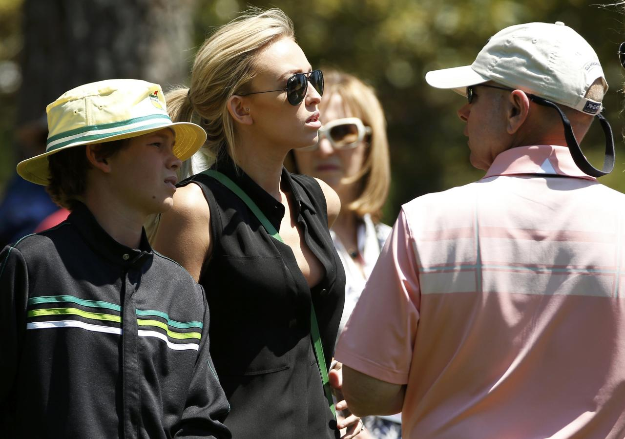 Paulina Gretzky (C) is accompanied by her brother Tristan (L) as she watches her fiance Dustin Johnson (not shown) play on the second hole during the first round of the 2014 Masters golf tournament at the Augusta National Golf Club in Augusta, Georgia April 10, 2014. REUTERS/Jim Young (UNITED STATES - Tags: SPORT GOLF)
