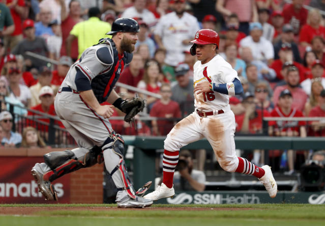 St. Louis Cardinals' Kolten Wong, right, scores past Atlanta Braves catcher Brian McCann during the fourth inning of a baseball game Sunday, May 26, 2019, in St. Louis. (AP Photo/Jeff Roberson)
