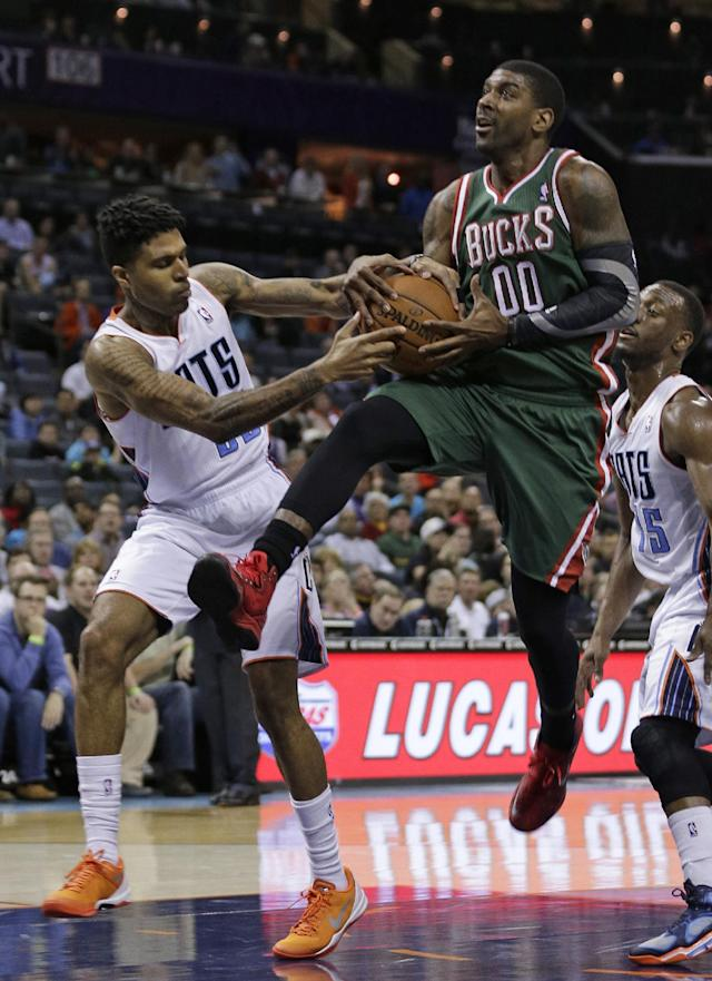 Milwaukee Bucks' O.J. Mayo (00) is tied up by Charlotte Bobcats' Chris Douglas-Roberts (55) during the second half of an NBA basketball game in Charlotte, N.C., Monday, Dec. 23, 2013. The Bobcats won 111-110 in overtime. (AP Photo/Chuck Burton)