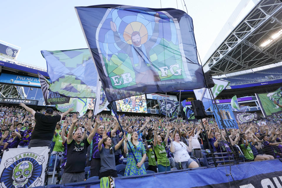 FILE - In this July 25, 2021, file photo, members of the Emerald City Supporters and other fans wave flags and cheer before an MLS soccer match between the Seattle Sounders and Sporting Kansas City in Seattle. Fans attending most pro sporting events in Seattle will soon be required to show proof they've been vaccinated against COVID-19 or that they've tested negative for the virus. The NFL's Seahawks, MLS's Sounders, NHL's Kraken and the University of Washington all announced updated policies Tuesday, Sept. 7, 2021, for fans attending games this season. (AP Photo/Ted S. Warren, File)