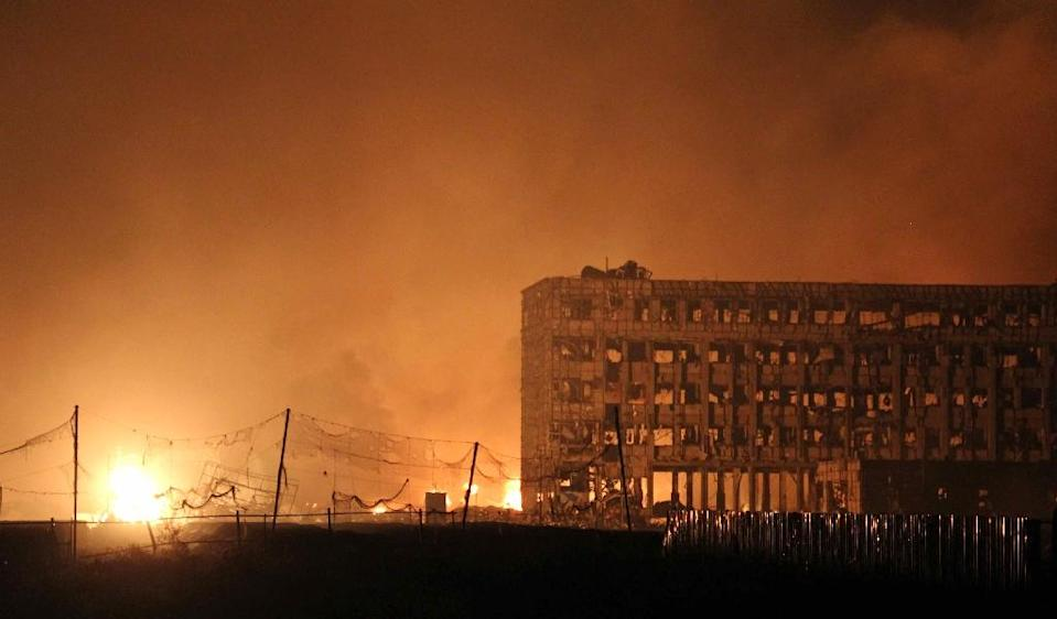 Flames rise next to a damaged building at the site of a series of explosions in Tianjin, early on August 13, 2015 (AFP Photo/-)