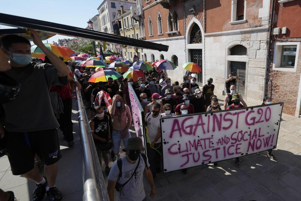 Demonstrators holds rainbow umbrellas during a protest against the G20 Economy and Finance ministers and Central bank governors' meeting in Venice, Italy, Saturday, July 10, 2021. (AP Photo/Luca Bruno)