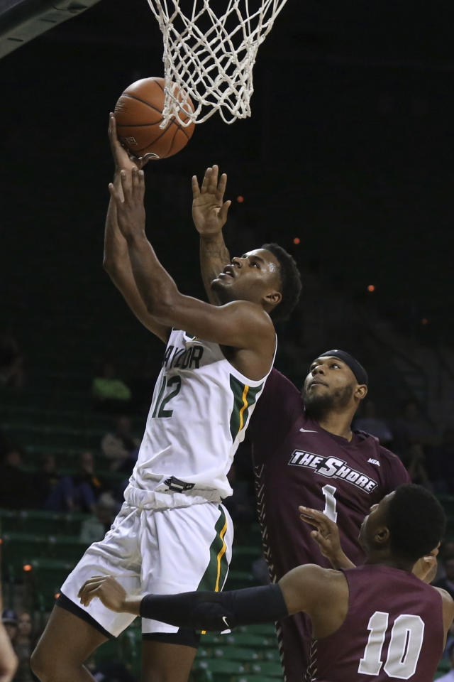 Baylor guard Jared Butler, left, scores past Maryland-Eastern Shore forward Marlon Adams and guard Glen Anderson, right, in the second half of an NCAA college basketball game, Tuesday, Dec. 3, 2019, in Waco, Texas. Baylor won 78-46. Butler scored a game high 20 points.(AP Photo/Rod Aydelotte)