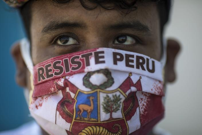 """John Sanchez wears a face mask with the Spanish message """"Resist Peru"""" as he waits in line to be tested for COVID-19 at Almenara Hospital in Lima, Peru, Friday, April 24, 2020. (AP Photo/Rodrigo Abd)"""