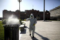A man sprays bleach at Plaza de Mayo in Buenos Aires, Argentina, Friday, March 20, 2020. Argentina's government imposed a countrywide lockdown to contain the spread of the coronavirus. (AP Photo/Natacha Pisarenko)