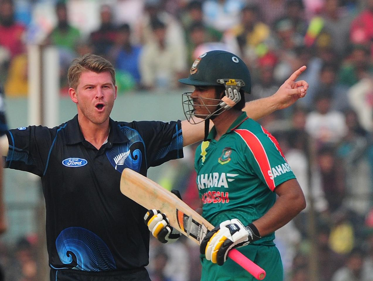 New Zealand bowler Corey Anderson (L) celebrates after the dismissal of Bangladesh batsman Shamsur Rahman (R) during the third One-Day International (ODI) cricket match between Bangladesh and New Zealand at Khan Jahan Ali Stadium in Fatullah on the outskirts of Dhaka on November 3, 2013 . AFP PHOTO/ Munir uz ZAMAN        (Photo credit should read MUNIR UZ ZAMAN/AFP/Getty Images)