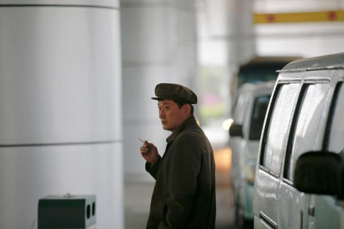FILE PHOTO: A man smokes a cigarette outside the airport in Pyongyang