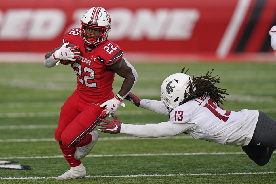 Utah running back Ty Jordan (22) runs for a score as he eludes a tackle by Washington State linebacker Jahad Woods (13) during the second half of an NCAA college football game Saturday, Dec. 19, 2020, in Salt Lake City. (AP Photo/Rick Bowmer)